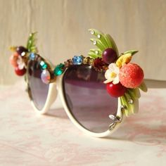 TEXTURE: When looking at these sunglasses one can feel the smooth surface of the frame and the lenses but the rough and pocky surface of the decoration. The peach looks like it's covered with some dust, so one knows that feel like somewhat used sandpaper.
