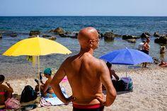Fotografía de un hombre frente a dos sombrillas para explicar cómo construir a combinar primer plano y fondo.