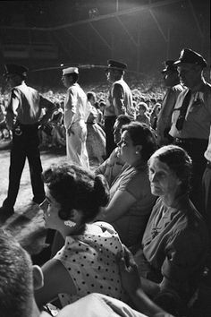 """Guarded Elvis Family Watch -   Members of Elvis' immediate family watch from off stage while Elvis performs. They are well protected by local police and Navy shore Patrol. Russwood Park, Memphis, TN. July 4,1956. Left - Barbara Hearn (girlfriend), Minnie Mae """"Dodger"""", and Gladys."""