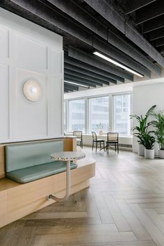 """Furnishings that add to the """"boutique sensibility"""" of this office include a series of small, black cafe tables and rattan chairs, curved wood booths and a built-in bench that runs across a wall. Round terrazzo tables attach to the built-in structure with rods in a hooked shape for support. New York Office, Long Room, Curved Wood, Cafe Tables, Cafe Style, Built In Bench, Architecture Office, Office Interiors, Corporate Interiors"""