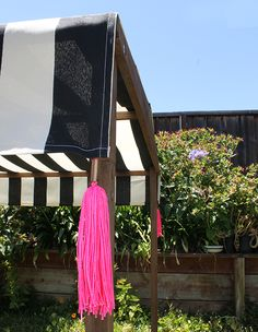 A DIY Canopy with black and white stripes and hot pink tassels #LowesCreator