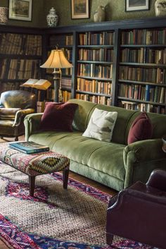 Lived in library with plush green sofa, leather side chairs, green wallpaper, bookshelves, patterned ottoman and rug. velvet couch, home libraries, dream, bookcas, reading books