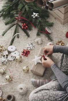 Picture of a woman wrapping Christmas gifts next to decorations by gpointstudio on Envato Elements