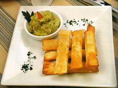 Tequenos Peruvian Appetizer - Easy to make! Wanton wrapped mozzarella and guacamole dipping sauce.