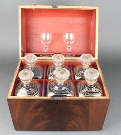 Lot 102, A 19th Century mahogany dome topped liqueur box containing 6 square gilt decorated decanters with mushroom stoppers and 2 spirit glasses £250-300