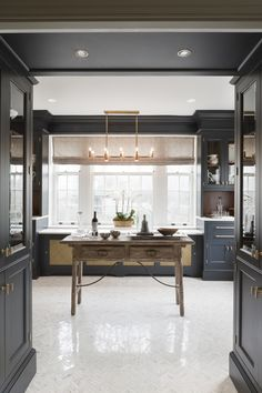 My parents might like this! New vintage navy cabinets, Calcutta marble floors, brass fixtures. Butler's pantry by Nadia Subaran.