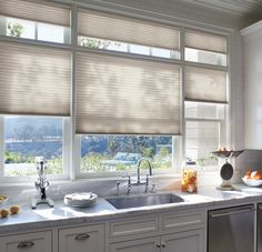 Kitchen windows covered with Hunter Douglas Duette shades.  These shades are not only available with cordless and motorized options, but are energy efficient too!