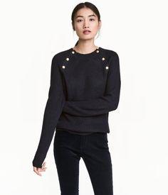 Gråmelerad. En stickad tröja i mjuk kvalitet med inslag av ull. Tröjan har metallknappar upptill och lång raglanärm. Ribbstickad kant kring halsringning,