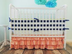A ruffled crib skirt adds a sweet, girly touch to the nursery. Plus, we are loving this coral and navy custom bedding from @Tushies And Tantrums!