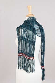 This scarf/wrap pattern starts as a tube worked in-the-round until it measures 12 to 14 inches. The width of the tube is then cut to form a flat piece. Then, sets of stitches are dropped from the needle to form the long strands shown in the photos.
