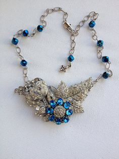 This necklace was made with Art Deco rhinestone flower and leaf dress clips, with an antique Bermuda blue rhinestone flower focal. This 3 1/3