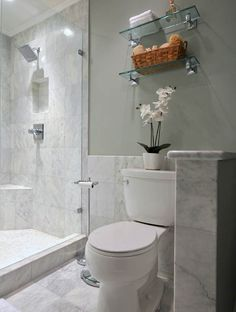 Love this #marble #bathroom with walk-in #shower, glass #shelves, and a pretty #orchid on display