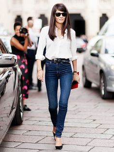 A white button-down shirt is paired with belted high waisted skinny jeans and black pumps