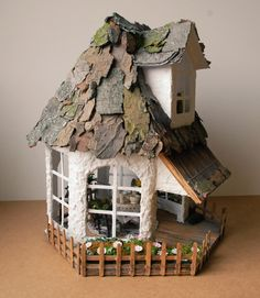 This adorable handmade summer cottage is completely furnished and waiting for a fairy to move in. It's made of wood and the roof is covered with