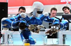 "Fair visitors look at the humanoid robotic system ""Rollin' Justin"" preparing a tea on March 2, 2009 at the world's biggest high-tech fair CeBIT in Hanover, central Germany. (RONNY HARTMANN/AFP/Getty Images) #"