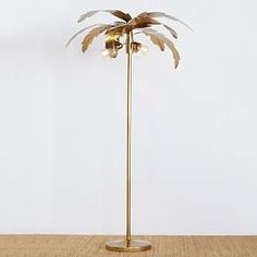The Emily & Meritt Palm Floor Lamp: Light up your space with a touch of the tropics! Our sturdy, hand-painted floor lamp glistens with a pretty gilded finish and cool, palm-inspired details. Imagined exclusively for PBteen by celebrity stylists and fashion designers Emily Current and Meritt Elliott, it captures their classic and rebellious aesthetic.
