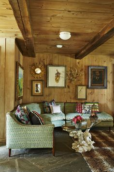 A wood paneled living room with stone floors, upholstered sofa, and a wall of framed art and sculptural mirrors. | Lonny.com