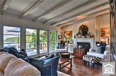 Laguna Beach Ca. - designer Susie Mitchell. Love the chairs and pillows.  Two window coverings similar to wood floor color.