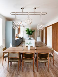 In the open-plan kitchen, a trio of ring-shaped pendant lamps made bespoke by Home Studios dangle above a walnut dining table. The nickel and brass spotlights that illuminate the central breakfast island were also crafted by the studio.