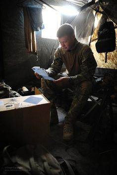 A soldier with 1st Battalion The Scots Guards reads a letter from home known as a 'bluey' while in his accommodation in Afghanistan.