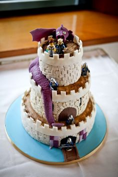 Medieval LEGO Wedding cake shaped like a castle, with banners, LEGO knights, a LEGO king and queen and an adorable purple dragon.
