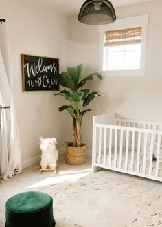 modern boho baby boy neutral nursery with faux plants, white crib and modern details