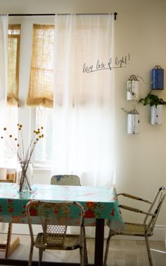 burlap and cheesecloth window covering. could do this with burlap and lace in bathroom. love the oilcloth on table and the metal chairs.