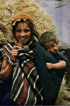 Africa: Smiles and tattoos, African Berber girl and sibling, colored vintage photo, Atlas Mountains, Morocco