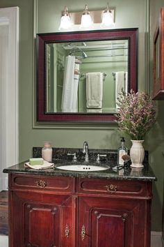 In this master bath, a vintage cabinet was converted to a vanity and paired with a mirror framed in a matching finish. | Photo: Mark Lohman