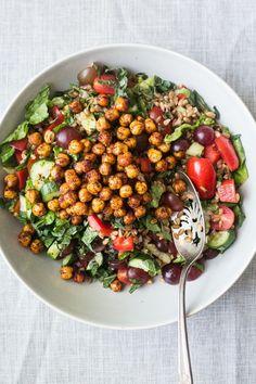 Une magnifique salade de farro, tomates, concombre, raisins & pois chiches épicés croustillants, avec une délicieuse vinaigrette au sumac et citron. (Vegan)