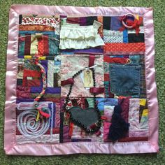 This one of a kind handmade quilt has many items to help soothe anxious hands and nervousness in people with Alzheimers Disease, stroke, dementia, Autism, or other brain trauma issues. This quilt is approximately 27 square. It is backed with soft burgandy, black and white plaid flannel.  The nine squares feature the following;  * Top left patchwork square has rick rack ribbons with a bobbin and a wooden spool that slide and spin. * Middle top square has a smaller patchwork mini with white…