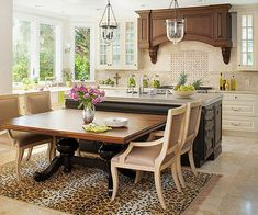 A standard dining table and area rug set against the island give the illusion of one large furniture piece. Simply pull the table away and add more chairs for larger occasions.