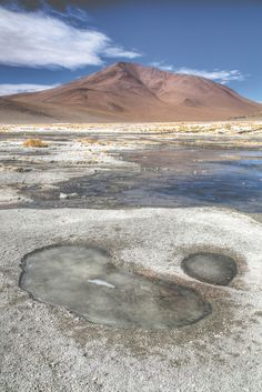 Bolivian landscape - frozen lakes and red desert volcanos.  See more on our blog.