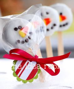 snowman pops made out of oreos dipped in icing w/ chocolate chips and candy corn for the face!!