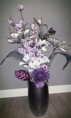 Foambloemstuk met paars / grijze bloemen en decoratie takken in een ...