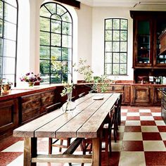 Love the arched windows, long table and wooden cabinetry. Inviting, country-style kitchen!