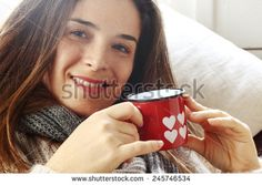 smiling girl drinking something over sofa from Valentine heart painted glass