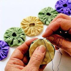 Making Yo-Yos. What? I have never seen these! The wall art hanging I've seen on Pinterest is cute - but these would be so cute as drapes.