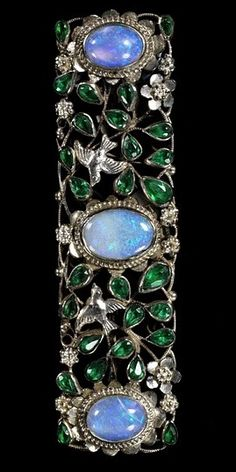 Brooch, circa 1922, by Arthur and Georgie Gaskin. Silver wire, opals, glass imitation emeralds.