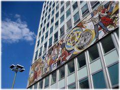 """Symbole für das Forschen und Lehren im Arbeiter- und Bauernstaat DDR. Diese Wandbilder finden sich am """"Haus des Lehrers"""" am Alexanderplatz in Berlin. Das Haus des Lehrers war für Schulungen und Kongresse der Lehrer der DDR gedacht. Das Foto zeigt das Wandbild von Walter Womacka."""