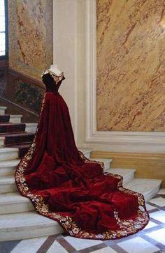 Traîne de dame d'honneur des Impératrices de Russie =  velours de soie couleur cerise/brodée sur le pourtour d'une guirlande de fleurs/Corsage baleiné à grand décolleté