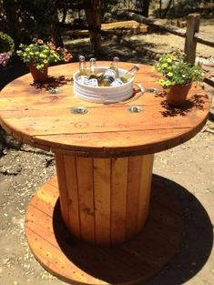 Wooden spool table.  Sanded and stained the spool.  Cut a hole in the middle and dropped in a 5-gallon paint bucket as a beer cooler! by aciendo