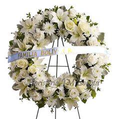 Las coronas de flores blancas son las mas solicitadas por la pureza de expresión que se quiere enviar. viene armada con rosas y lirios blancos.     Soportada en un pedestal, el cual facilita ponerla en cualquier parte de la sala fúnebre.     La cinta marcada con el nombre del remitente muestra el aprecio de quien la está enviando.    Corona fúnebre de flores blancas con pedestal y cinta para enviar a la funeraria en Bogota. Coronas Flores Blancas (Inc. Pedestal + Cinta Marcada): Desde USD$68