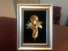 Vintage gold tone flower pins on velvet mat. Used a pretty but inexpensive gold tone frame