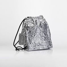 This gym bag backpack made of an innovative aluminum canvas features a drawstring closure. In 2014 alongside their clothing line, Je Suis Belle designed a bag collection together with Gabriella Veszpr_mi, one of the founders of Komod. The playful shapes that evoke shopping bags, lunch bags and plastic bags, have been realized using innovative aluminum coated canvas which obtains its real character through usage by creases and surface fragmentation.