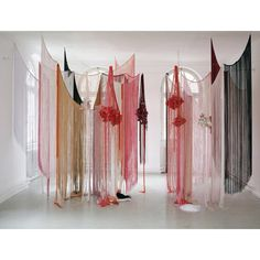 This an an installation art piece by Angelika Arendt.  A very peaceful entrance or frame for a ritual space. Fringed curtains intermingled with hanging dried flower bouquets surrounded by beautiful natural light in a windowed room.
