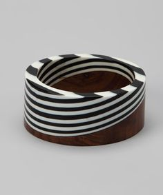 Zad Black & White Stripe Resin Bangle by ZAD on #zulily. Reg $21. Now $10.99. Smooth, organic appeal defines this carved bracelet. Polished black & white resin blends seamlessly into the rich hardwood to create a unique accent.   Size: 1.25'' wide, 2.75'' diameter  Made of: Resin / wood  Imported. (3/1/13)
