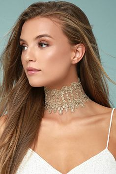 "The Queenly Gold Lace Choker Necklace makes your royal status known! A 3"" wide band of metallic gold lace has fringe and scalloped edges. Necklace measures 10"" long with a 5"" extender chain."