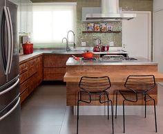 No projeto da designer de interiores Magda Marconi, tanto os armários quanto a ilha são de madeira de demolição. A cor no ambiente fica por conta das pastilhas de vidro que revestem as paredes.