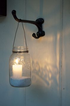 Mason jar votive candle holders at night. Sand and a citronella candles in mason jars hung from plant hangers.